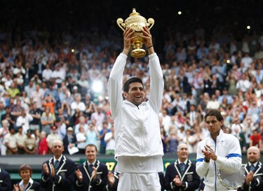 Novak Djokovic of Serbia holds the winners trophy after defeating Rafael Nadal of Spain (R) in the men's singles final at the Wimbledon tennis championships in London on July 3, 2011. (REUTERS)