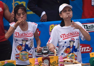 """Juliet Lee (L) and Sonya """"The Black Widow"""" Thomas compete in the Women's 2011 Nathan's Famous Fourth of July International Hot Dog Eating Contest at Coney Island, Brooklyn, New York July 4, 2011. REUTERS/Allison Joyce"""
