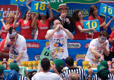 Joey Chestnut (C) competes in the 2011 Nathan's Famous Fourth of July International Hot Dog Eating Contest at Coney Island, Brooklyn, New York July 4, 2011. REUTERS/Allison Joyce