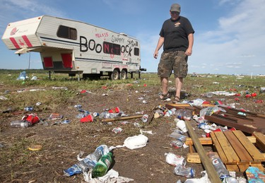 Dean Minault, the cousin of Colin Kobza, the organizer of Boonstok, looks at all of the garbage left behind by the Boonstock music festival that happened on the Canada Day weekend in a field just outside of Gibbons, AB, on July 4, 2011. The massive area is covered in trash including abandoned cars, beer bottles, and even RV's left behind. LAURA PEDERSEN/EDMONTON SUN QMI AGENCY
