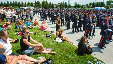 Police and civilians watch the funeral for York Polic Const. Garrett Styles on a screen outside the Ray Twinney Recreation Complex, in Newmarket on July 5, 2011. (ERNEST DOROSZUK/QMI Agency/Toronto Sun)