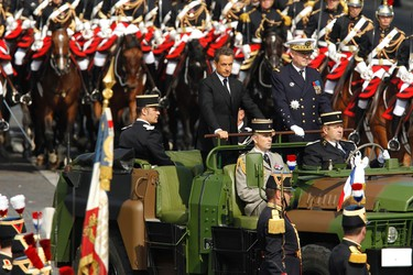 France's President Nicolas Sarkozy rides down the Champs Elysee in a military command car during the traditional Bastille Day parade in Paris, July 14, 2011. REUTERS/Benoit Tessier