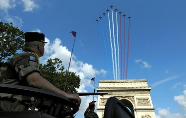 Alphajets trail France's national colours over the Champs Elysee during the traditional Bastille Day parade in Paris, July 14, 2011.  REUTERS/Philippe Wojazer
