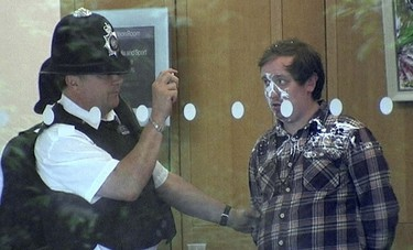 A man is photographed by police officers after he tried to attack News Corp Chief Executive and Chairman Rupert Murdoch with a white substance during a parliamentary committee hearing on phone hacking at Portcullis House in London July 19, 2011.  Murdoch was attacked by a protester on Tuesday while giving evidence to a British parliamentary committee at which he defended his son and his company over a scandal that has rocked the British establishment.  REUTERS/UK Pool via Reuters TV