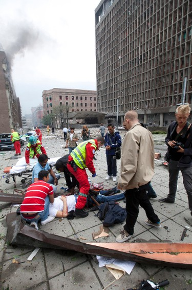 Injured people are treated by medics at the scene of an explosion near the government buildings in Norway's capital Oslo on July 22, 2011. At least one person was killed by the powerful explosion which ripped through government and media buildings. AFP PHOTO / SCANPIX / HOLM MORTEN