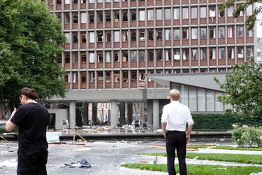 People look at a damaged government building after a powerful explosion rocked government and media buildings in Norway's capital Oslo on July 22, 2011. At least one person was killed by the powerful explosion which ripped through government and media buildings. AFP PHOTO / SCANPIX / MARIANNE LOVLAND