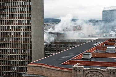 """Smoke rises from a building after a powerful bomb blast rocked government and media buildings in Norway's capital Oslo on July 22, 2011, causing """"deaths and injuries"""" and dealing heavy damage, police said. Police said a bomb was behind the explosion and Norwegian media reported that at least two people died. AFP PHOTO / ALEKSANDER ANDERSEN"""