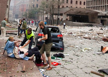 An injured man is attended to at the site of a powerful explosion that rocked central Oslo July 22, 2011. (Reuters)