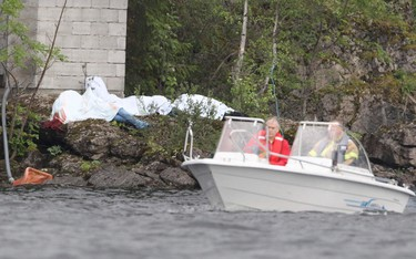 A rescue boat passes by covered corpses on the shore of the small, wooded island of Utoeya July 23, 2011. (Reuters)