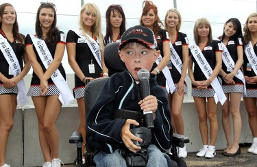 """Noah Johnsen, 9, says """"Drivers start your engines"""", during the start of the Firestone Indy Lights Race #1, Saturday July 23, 2011.  Johnsen has spinal muscular atrophy. Miss Edmonton Indy finalist are visible behind Johnsen. DAVID BLOOM EDMONTON SUN  QMI AGENCY"""