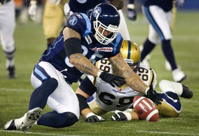 Toronto Argonauts Ricky Foley recovers a fumble by Winnipeg Blue Bomber Fred Reid in the first quarter of their CFL football game in Toronto Saturday. Foley was fined by the CFL for comments he made after the contest. (REUTERS/Fred Thornhill)