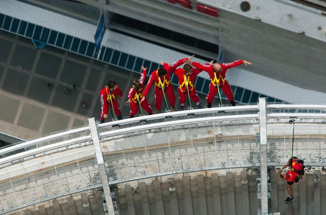 The Toronto Sun's Jenny Yuen (second from the left) hangs out over Toronto at the CN Tower's new EdgeWalk attraction. (MICHAEL PEAKE/Toronto Sun)
