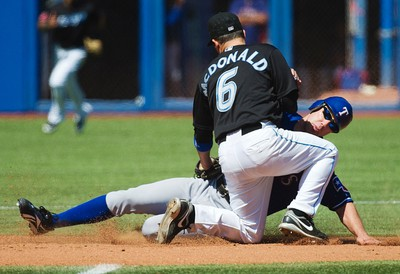 Toronto Blue Jays' John McDonald tags out Texas Rangers' Dave Murphy trying to steal second base during the ninth inning of their MLB American League baseball game in Toronto July 30, 2011. (REUTERS)