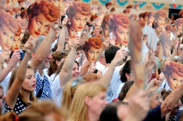 People hold up masks of Lucy Ball during an attempt to set a new Guinness world record for most Lucy Ricardo lookalikes assembled in one place, in Jamestown, New York August 6, 2011. (REUTERS/Doug Benz)