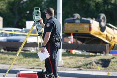 Winnipeg police Traffic Accident Investigators gather evidence at the site of a fatal crash at McPhillips Street and Jarvis Avenue Saturday morning. (Sebastien Perth/Winnipeg Sun/QMI Agency)
