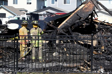 Firefighters look for hotspots at the scene of a fire that destroyed four homes and heavily damaged two others on Sunrose Lane in the Suntree subdivision of Leduc, Alberta, Sunday Aug. 21, 2011. No one was injured in the blaze. DAVID BLOOM EDMONTON SUN  QMI AGENCY