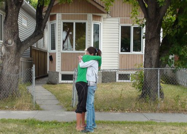Two women hug in front of a Garfield Street North home that was the backdrop of a deadly brawl involving two vehicles. A 17-year-old girl is accused of driving a van that killed a 40-year-old man. (Tamara King/Winnipeg Sun)
