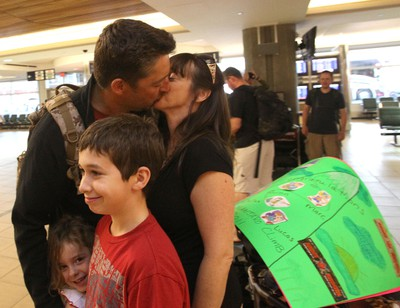 Warrant Officer Quinn Beggs (left) greets his wife Carol Beggs (right) with his family Maxine Beggs, 3 years, (front left) and James Maruca, 13 years (front right) after arriving at the Edmonton International Airport in Edmonton, AB as one of the four soldiers who represented the Canadian Forces on the Royal Alexandra Hospital Foundation Kilimanjaro Climb 2011 on August 21, 2011. LAURA PEDERSEN/EDMONTON SUN QMI AGENCY
