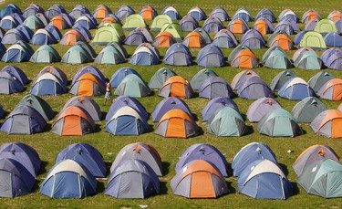 A man walks among some 300 tents, each for four people, in the 'Wiesn camp' at the Olympic Horse Stadium in Munich-Riem Sept. 13, 2011. The accommodation is mainly for backpackers and low-budget-tourists and costs between 58 euros and 68 euros per night.       REUTERS/Michaela Rehle