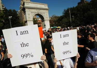 """Protesters hold signs during an """"Occupy Wall Street"""" rally in New York's Washington Square October 8, 2011. New York Mayor Michael Bloomberg accused anti-Wall Street protesters on Friday of trying to destroy jobs in the city, even as he said he was sympathetic to some of their complaints. REUTERS/Jessica Rinaldi"""