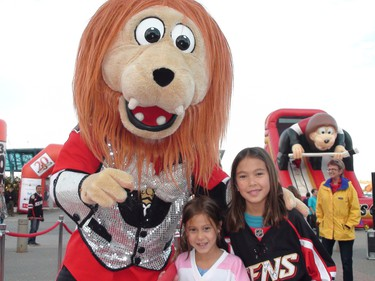 Oct. 11, 2011 -- Ottawa Senators fans were out in force for the team's home opener against the Minnesota Wild Tuesday. Spartacat meets fans Lia and Mei-Ling Pak outside Scotiabank Place. SCOTT TAYLOR/OTTAWA SUN/QMI AGENCY