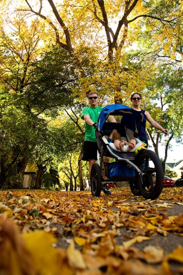 Nathan and Sarah Brandvold take Mattias, 1, for a walk along 81 Avenue as the leaves start to fall in Edmonton on Sept. 27, 2011. The young family was celebrating Mattias' first birthday. (CODIE MCLACHLAN/QMI AGENCY)