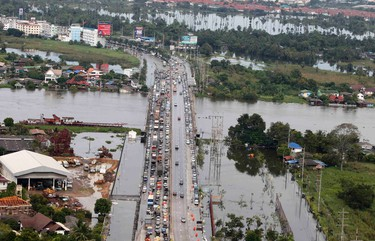 An aerial view of residents and vehicles being evacuated from a flooded area in Pathum Thani province, on the outskirts of Bangkok October 14, 2011. Thai Prime Minister Yingluck Shinawatra tried to reassure residents of Bangkok on Friday that the capital should largely escape the flooding that has covered a third of the country since July and caused damage of at least $3 billion.  REUTERS/Chaiwat Subprasom