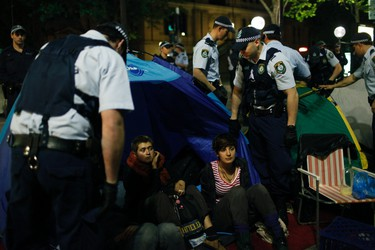 """Police officers remove camping gear from protesters of the """"Occupy Sydney"""" movement in front of the Reserve Bank of Australia in central Sydney October 15, 2011. Protesters worldwide geared up for a cry of rage on Saturday against bankers, financiers and politicians they accuse of ruining global economies and condemning millions to poverty and hardship through greed. REUTERS/Lukas Coch"""