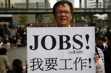 """An activist holding a placard reading """"I want a job!"""" takes part in a protest in front of the Taipei 101 building October 15, 2011. More than a hundred protesters gathered in front of Taiwan's landmark Taipei 101 building on Saturday in response to the global Occupy Together movement against unfair wealth distribution. Protesters worldwide geared up for a cry of rage on Saturday against bankers, financiers and politicians they accuse of ruining global economies and condemning millions to poverty and hardship through greed.     REUTERS/Pichi Chuang"""