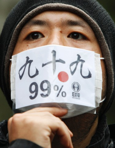 """An Occupy Tokyo protester wears a mask during a rally in Tokyo October 15, 2011. Protesters worldwide geared up for a cry of rage on Saturday against bankers, financiers and politicians they accuse of ruining global economies and condemning millions to poverty and hardship through greed. Galvanized by the past month's Occupy Wall Street movement, they plan to take to the streets from Sydney to Alaska via London, Frankfurt, Washington and New York. The characters on the mask, """"99%"""", streamed from the Occupy Wall Street movement, is a reference to the idea that the top 1 percent of Americans have too much. REUTERS/Issei Kato"""