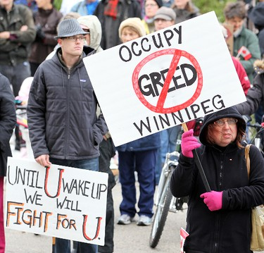 Protesters wave placards during the Occupy Winnipeg demonstration outside the Manitoba Legislative building in Winnipeg Saturday October 15, 2011. BRIAN DONOGH/QMI AGENCY