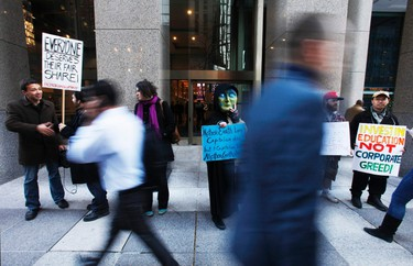 """Protesters stand outside the front of the TSX building during a small """"Occupy Toronto"""" rally in Toronto on October 17, 2011. (REUTERS/Mark Blinch)"""