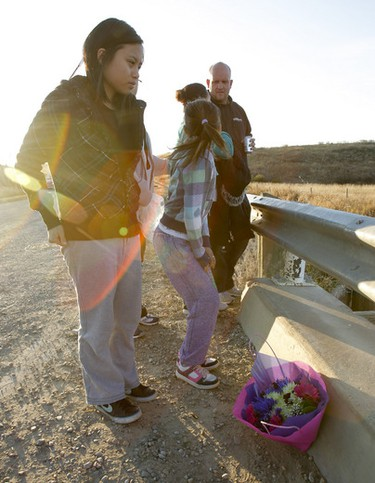Patricia Dainard lays flowers for her brother Renzo over Pothole Creek near Magrath, south of Lethbridge, on Sunday, October 16, 2011. Four teenagers, including Renzo, lost their lives in a rollover crash the night before, flipping upside down into Pothole Creek. (LYLE ASPINALL/QMI AGENCY)