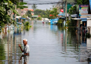 A man wades through water as soldiers arrive with aid to the isolated and flooded village of Kajee Nush in Pathum Thani province, in the outskirts of Bangkok, October 21, 2011. Thailand reported progress in diverting floodwater round its capital into the sea on Friday but the prime minister instructed troops to protect key buildings as her government struggled to contain the worst flooding in 50 years. REUTERS/Damir Sagolj (THAILAND - Tags: ENVIRONMENT DISASTER)