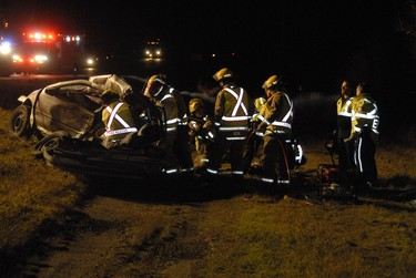 Emergency crews work quickly to extricate a patient trapped inside a car following a multi-vehicle collision south of Grande Prairie on the Correction Line near Highway 40 just after midnight Saturday, October 22, 2011. At least one was pronounced dead on scene and two were ejected from the vehicle. DAN ILIKA/DAILY HERALD-TRIBUNE/QMI AGENCY