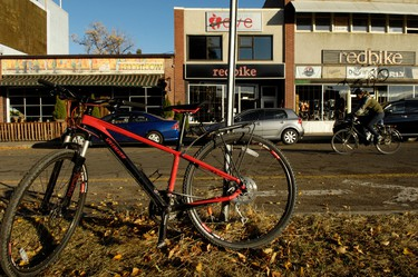 A cyclist passes in front of retail storefronts along 88 Avenue in Edmonton, Alberta, on Oct. 22, 2011. While cyclists have had to bundle up against falling temperatures, many Edmontonians continue to use their bikes this fall. IAN KUCERAK/EDMONTON SUN/QMI AGENCY