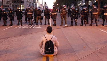 A man sits in front of a police line at City Hall during an anti-Wall Street protest in Oakland, California, October 25, 2011. (REUTERS/Kim White)