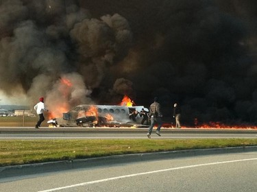 PHOTO OF THE WEEK OCTOBER 28 - Passersby run towards a burning King Air passenger plane to help rescue passengers Thursday October 27 2011 in Richmond BC. Seven passengers and a crew of two were in the plane. The pilot died later. QMI AGENCY/ WILSON CHAN