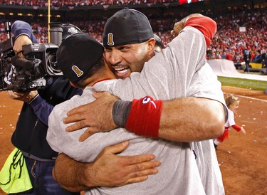 St. Louis Cardinals first baseman Albert Pujols R) celebrates with teammate after the Cardinals defeated the Texas Rangers to win MLB's World Series baseball championship in St. Louis, Missouri, October 28, 2011.   REUTERS/Jeff Haynes