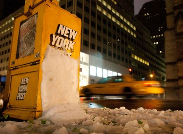 A taxi traverses down Fifth Avenue past a newsstand hit by snow in New York October 29, 2011. A rare October snowstorm barreled up the heavily populated U.S. East Coast on Saturday, threatening up to a foot (30 cm) of snow, cutting power to nearly a million households and forcing at least 1,000 flight cancellations.  REUTERS/Andrew Kelly