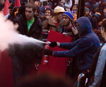 A protester uses a fire extinguisher smoke against the police officers outside the offices of Jean Charest during a student demonstration in downtown Montreal, Quebec, November 10, 2011. (PHILIPPE-OLIVIER CONTANT/QMI AGENCY)