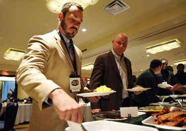 Winnipeg Blue Bombers' head coach Paul LaPolice (R) watches his quarterback Buck Pierce take food during their team breakfast in Vancouver, British Columbia, November 24, 2011. The Winnipeg Blue Bombers will play the BC Lions at BC Place in the CFL's 99th Grey Cup football game on Sunday. (REUTERS)
