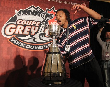 Winnipeg Blue Bombers Kenny Mainor hams it up with the Grey Cup is  in Vancouver, B.C. Nov 23, 2011 during a team media breakfast. Winnipeg Blue Bombers and the B.C. Lions battle Sunday for the Grey Cup.  (ANDRE FORGET /QMI AGENCY)