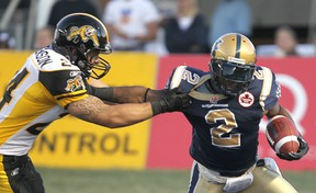 Winnipeg Blue Bombers Jovon Johnson breaks a tackle by Hamilton Tiger-Cats Daryl Stephenson during CFL action in Winnipeg Friday August 26, 2011. (BRIAN DONOGH/QMI Agency)