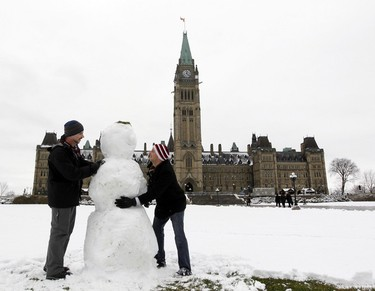 OTTAWA 01- Ian Murphy (left) and Tom Shock (right) put the finishing touches on their snowman they built on the front lawn of Parliament Hill, in Ottawa November 23, 2011.     Chris Roussakis/QMI Agency