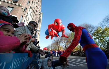 A Spiderman performer greets children as the Spiderman balloon floats down Central Park West during the 85th Macy's Thanksgiving day parade in New York November 24, 2011. REUTERS/Gary Hershorn
