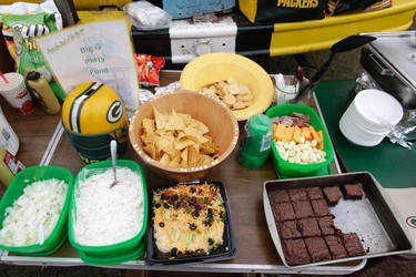 A table with food for tailgaters is seen before the start of the NFL football game between the Green Bay Packers and the Tampa Bay Buccaneers in Green Bay, Wisconsin November 20, 2011. Forget their 11-0 record. The most interesting thing about this year's Green Bay Packers may be the way the football team is reuniting -- in a small way - the people of Wisconsin, who have been torn apart so dramatically in 2011 by politics. Photo taken November 20.  REUTERS/Darren Hauck/Files (UNITED STATES - Tags: SPORT FOOTBALL FOOD)