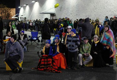 """Shoppers watch a movie on a screen while waiting in line for """"Black Friday"""" sales outside the Best Buy electronics store in Westbury, New York. (REUTERS/Shannon Stapleton)"""