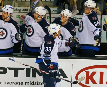 Winnipeg Jets defenseman Dustin Byfuglien (33) is congratulated by teammates after scoring against the Boston Bruins in first period action during their NHL hockey game in Boston, Massachusetts November, 26 2011.    REUTERS/Adam Hunger  (UNITED STATES - Tags: SPORT ICE HOCKEY)