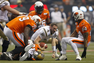 Winnipeg Blue Bombers quarterback Buck Pierce (C) loses his helmet after being tackled by BC Lions' Eric Taylor (L) and Korey Banks (R) in the first half of the CFL's 99th Grey Cup football game in Vancouver, British Columbia November 27, 2011. REUTERS/Ben Nelms (CANADA  - Tags: SPORT FOOTBALL)